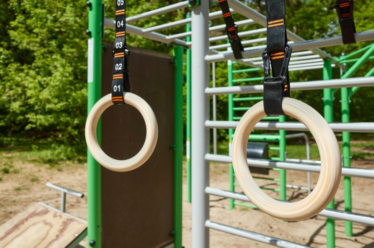 Wooden gymnastic rings hanging in a open air gym.
